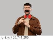 Купить «smiling man with mustache and bowtie party props», фото № 33741286, снято 22 февраля 2020 г. (c) Syda Productions / Фотобанк Лори