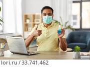 Купить «man in mask with hand sanitizer at home office», фото № 33741462, снято 4 апреля 2020 г. (c) Syda Productions / Фотобанк Лори