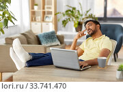 Купить «man with laptop resting feet on table at home», фото № 33741470, снято 4 апреля 2020 г. (c) Syda Productions / Фотобанк Лори