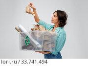 Купить «happy smiling young woman sorting paper waste», фото № 33741494, снято 18 апреля 2020 г. (c) Syda Productions / Фотобанк Лори