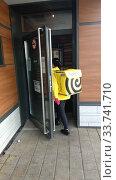 Курьер Яндекс-доставки заходит в Макдональдс.  Кафе закрыто, работает только на доставку. (2020 год). Редакционное фото, фотограф Ирина Терентьева / Фотобанк Лори