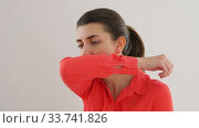 woman coughing covering mouth with elbow. Стоковое видео, видеограф Syda Productions / Фотобанк Лори