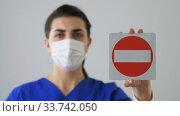 Купить «doctor or nurse in face mask showing stop sign», видеоролик № 33742050, снято 5 апреля 2020 г. (c) Syda Productions / Фотобанк Лори