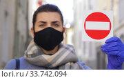 Купить «woman in face mask with stop sign in city», видеоролик № 33742094, снято 12 апреля 2020 г. (c) Syda Productions / Фотобанк Лори