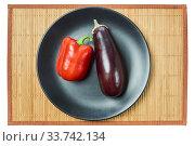 Купить «Purple eggplant and red bell pepper on a gray plate on a cane tablecloth», фото № 33742134, снято 10 мая 2020 г. (c) Евгений Харитонов / Фотобанк Лори