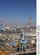 Купить «Four-link cargo loading crane on dock with parked motor vehicles ready for shipping plus container loading cranes in background, Ashdod Port, Israel.», фото № 33744302, снято 4 октября 2019 г. (c) age Fotostock / Фотобанк Лори
