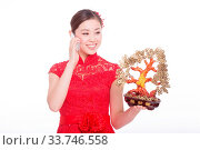 Купить «Young asian woman in red cheongsam holds mobile phone and lucky tree in chinese new year», фото № 33746558, снято 14 июля 2020 г. (c) age Fotostock / Фотобанк Лори
