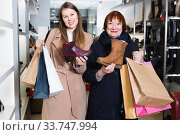 Young female with her mother are choosing shoes together in shoes shop. Стоковое фото, фотограф Яков Филимонов / Фотобанк Лори
