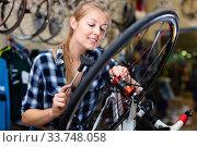 Купить «Female is fixing wheels of bicycle in workshop.», фото № 33748058, снято 13 сентября 2017 г. (c) Яков Филимонов / Фотобанк Лори