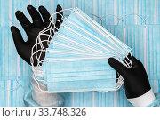 Купить «Doctor holding lot blue surgical medical face masks in black protective glove in hands», фото № 33748326, снято 8 мая 2020 г. (c) А. А. Пирагис / Фотобанк Лори