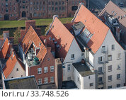 Lubeck, Germany. Red tiled roofs of old houses in the Old Town (2018 год). Стоковое фото, фотограф Наталья Николаева / Фотобанк Лори