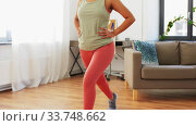 Купить «african woman doing lunge exercise at home», видеоролик № 33748662, снято 28 марта 2020 г. (c) Syda Productions / Фотобанк Лори