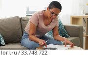 Купить «african woman with papers and calculator at home», видеоролик № 33748722, снято 28 марта 2020 г. (c) Syda Productions / Фотобанк Лори