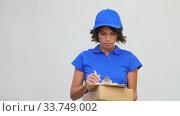 Купить «happy delivery girl with parcel box and clipboard», видеоролик № 33749002, снято 9 апреля 2020 г. (c) Syda Productions / Фотобанк Лори