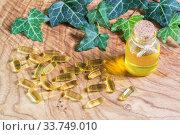 На деревянном фоне прозрачные желатиновые капсулы и флакон с рыбьим жиром. Омега-3 - незаменимые полиненасыщенные жирные кислоты. Листья плюща (лат. Hedera) Стоковое фото, фотограф Наталья Гармашева / Фотобанк Лори