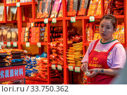Chongqing, China - August 2019 : Chinese woman selling snacks from her little shop on the street in Chongqing town. Стоковое фото, фотограф Zoonar.com/Pawel Opaska / age Fotostock / Фотобанк Лори
