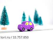Купить «Wooden car on paper road against fir-trees on white background. Traffic on country road», фото № 33757850, снято 13 мая 2020 г. (c) Papoyan Irina / Фотобанк Лори