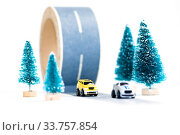 Купить «Two small cars on paper road against fir-trees on white background. Traffic on country road. Travel. Automotive exhaust pollution», фото № 33757854, снято 13 мая 2020 г. (c) Papoyan Irina / Фотобанк Лори