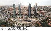 Купить «High view of four modern business skyscrapers (Cuatro Torres) in Madrid, Spain», видеоролик № 33758202, снято 6 августа 2020 г. (c) Яков Филимонов / Фотобанк Лори