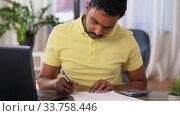 Купить «man with calculator and papers working at home», видеоролик № 33758446, снято 26 апреля 2020 г. (c) Syda Productions / Фотобанк Лори