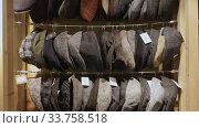 Купить «Large assortment of flat caps hanging on showcase in clothes shop», видеоролик № 33758518, снято 6 июля 2020 г. (c) Яков Филимонов / Фотобанк Лори