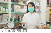 Portrait of chinese female druggist in protective facial mask working in pharmacy. Стоковое видео, видеограф Яков Филимонов / Фотобанк Лори
