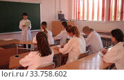 Купить «Attractive young asian female student standing in classroom full of students», видеоролик № 33758602, снято 24 сентября 2019 г. (c) Яков Филимонов / Фотобанк Лори