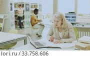 Купить «Mature teacher engaged in a public library», видеоролик № 33758606, снято 31 мая 2020 г. (c) Яков Филимонов / Фотобанк Лори