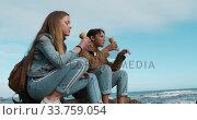 Купить «Side view of a Caucasian and a mixed race girl eating ice cream seaside», видеоролик № 33759054, снято 9 августа 2019 г. (c) Wavebreak Media / Фотобанк Лори