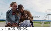 Купить «Front view of a Caucasian and a mixed race girl taking selfie on a merry-go-round», видеоролик № 33759062, снято 9 августа 2019 г. (c) Wavebreak Media / Фотобанк Лори