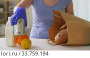 woman in gloves taking food from paper bag at home. Стоковое видео, видеограф Syda Productions / Фотобанк Лори