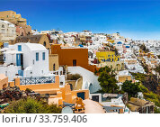 View of the city of Oia with white buildings, hotels, cafes and restaurants. Santorini, Greece (2017 год). Стоковое фото, фотограф Наталья Волкова / Фотобанк Лори