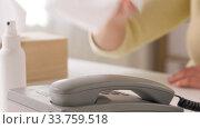 Купить «close up of woman cleaning phone with sanitizer», видеоролик № 33759518, снято 10 мая 2020 г. (c) Syda Productions / Фотобанк Лори