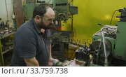 Купить «Caucasian male factory worker at a factory sitting at a workbench and operating machinery», видеоролик № 33759738, снято 23 ноября 2019 г. (c) Wavebreak Media / Фотобанк Лори