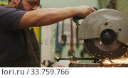 Купить «Caucasian male factory worker at a factory standing at a workbench and cutting a metal », видеоролик № 33759766, снято 23 ноября 2019 г. (c) Wavebreak Media / Фотобанк Лори