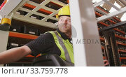 Caucasian male factory worker at a factory with a hat and high vis vest, using a truck. Стоковое видео, агентство Wavebreak Media / Фотобанк Лори