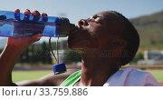 Купить «Disabled mixed race man with prosthetic legs sitting on a race track and drinking water», видеоролик № 33759886, снято 17 марта 2020 г. (c) Wavebreak Media / Фотобанк Лори