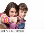 Мама прищурившись указывает пальцем в кадр, дочка с прищуром также смотрит в кадр. Стоковое фото, фотограф Иванов Алексей / Фотобанк Лори