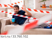 Купить «Young man feeling bored at home in self-isolation concept», фото № 33760102, снято 1 апреля 2020 г. (c) Elnur / Фотобанк Лори