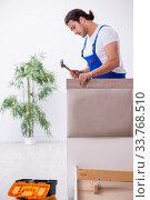 Купить «Young male contractor installing furniture at home», фото № 33768510, снято 11 ноября 2019 г. (c) Elnur / Фотобанк Лори