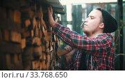 Купить «Young man woodcutter putting logs on the stand with other logs», видеоролик № 33768650, снято 2 июня 2020 г. (c) Константин Шишкин / Фотобанк Лори
