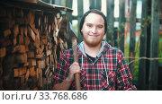 Купить «Young smiling man woodcutter with ax standing in front of the camera», видеоролик № 33768686, снято 2 июня 2020 г. (c) Константин Шишкин / Фотобанк Лори