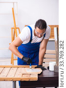 Young male contractor working in workshop. Стоковое фото, фотограф Elnur / Фотобанк Лори