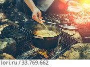 Купить «Девушка турист готовит обед на костре в походе», фото № 33769662, снято 30 апреля 2020 г. (c) Сергей Тиняков / Фотобанк Лори