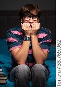 Купить «Young handsome student preparing for exams at night», фото № 33769962, снято 18 сентября 2018 г. (c) Elnur / Фотобанк Лори
