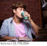 Купить «Young handsome student preparing for exams at night», фото № 33770054, снято 28 августа 2018 г. (c) Elnur / Фотобанк Лори