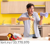 Купить «Young man calculating expences for vegetables in kitchen», фото № 33770970, снято 3 августа 2018 г. (c) Elnur / Фотобанк Лори