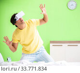 Купить «Young man with virtual glasses in the bedroom», фото № 33771834, снято 22 июня 2018 г. (c) Elnur / Фотобанк Лори