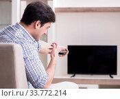 Купить «Young man watching tv at home», фото № 33772214, снято 9 марта 2018 г. (c) Elnur / Фотобанк Лори