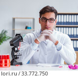 Young doctor working in the lab with microscope. Стоковое фото, фотограф Elnur / Фотобанк Лори